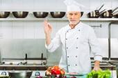 hezký usmívající se muž kuchař v jednotné pohledu kamery a zobrazení ok znamení v kuchyni restaurace