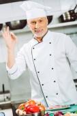 gut aussehend lächelnd männlichen Koch in einheitlichen Blick in die Kamera und ok Anzeichen in Restaurantküche