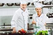 usmíval se ženské a mužské kuchaři v uniformě a klobouky pohledu kamery při vaření v kuchyni restaurace