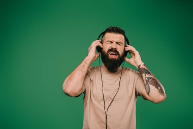 handsome tattooed man singing and listening music in headphones isolated on green