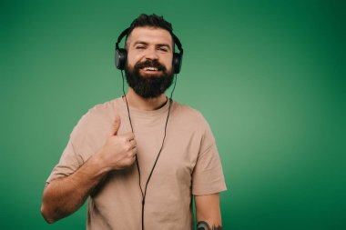 bearded smiling man showing thumb up while listening music in headphones isolated on green