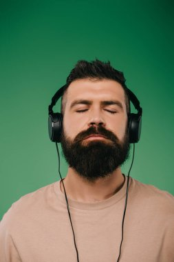 bearded man with closed eyes listening music in headphones isolated on green