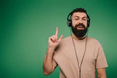 happy bearded man listening music in headphones and pointing up, isolated on green