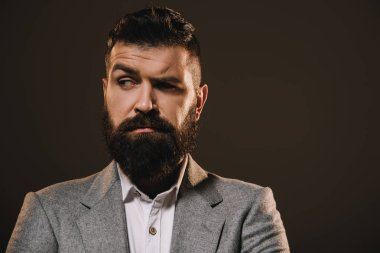 brunette beard businessman thinking isolated on brown