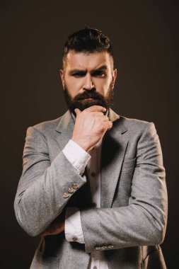 handsome beard businessman thinking and looking at camera isolated on brown