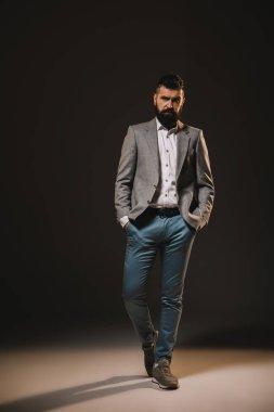Handsome beard businessman posing in jacket on brown stock vector
