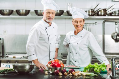 female and male chefs in uniform and hats looking at camera during cooking in restaurant kitchen