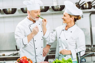 smiling female chef holding rosemary herb near man during cooking in restaurant kitchen