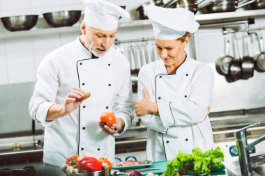 female and male chefs in double-breasted jackets and hats talking while cooking in restaurant kitchen