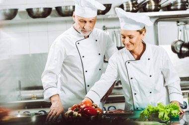 selective focus of female and male chefs in uniform and hats cooking in restaurant kitchen