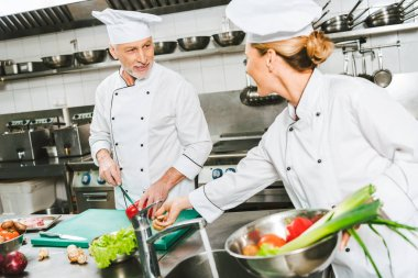 female and male chefs in uniform and hats looking at each other while cooking in restaurant kitchen