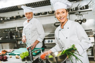 female and male chefs in double-breasted jackets and hats looking at camera while cooking in restaurant kitchen