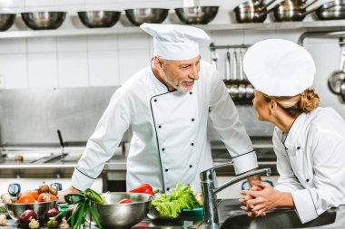 female and male chefs in uniform looking at each other while cooking in restaurant kitchen