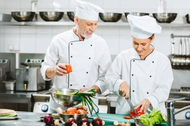 smiling female and male chefs in double-breasted jackets and hats cooking in restaurant kitchen