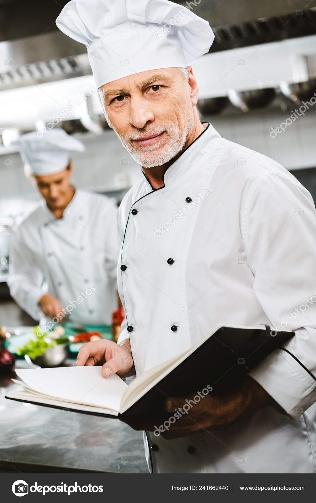 Male Chef Uniform Hat Looking Camera Holding Recipe Book