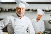 hezký mužský kuchař v uniformě a čepice s copy prostor při pohledu na fotoaparát v kuchyni restaurace