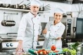 female and male chefs in uniform looking at camera during cooking in restaurant kitchen