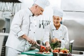 female and male chefs in uniform and hats cooking in restaurant kitchen