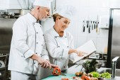Fotografie selective focus of female and male chefs in uniform using recipe book during cooking in restaurant kitchen