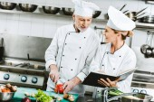 female and male chefs in uniform using recipe book during cooking in restaurant kitchen