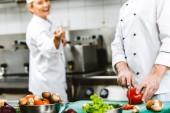 Fényképek Nézd a női és férfi szakácsok a kétsoros gombolású kabátok vágott étterem konyha főzés közben