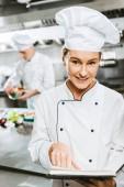 Fotografie krásná žena kuchař v jednotný recept knihu a při pohledu na fotoaparát v kuchyni restaurace