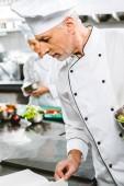 férfi szakács egyenruhát és kalap recept olvasó könyv étterem konyha