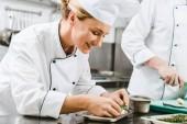 krásná usměvavá žena kuchař v uniformě dekorační misky s byliny v kuchyni restaurace