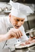 Fotografia cuoco unico maschio in uniforme condimento piatto nella cucina del ristorante