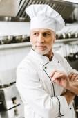 hezký mužský kuchař v uniformě a čepici koukal v kuchyni restaurace