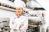 krásná usměvavá žena kuchař v uniformě s rukama zkříženýma na kameru v kuchyni restaurace