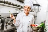 schönen lächelnden Köchin in Uniform mit Rosmarin und Schüssel mit Gemüse in Restaurantküche