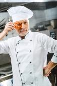 mužské kuchař v uniformě a klobouk drží pepř řezu před obličejem v kuchyni restaurace