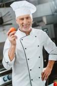 usmívající se muž kuchař v uniformě a klobouk drží rajče a při pohledu na fotoaparát v kuchyni restaurace