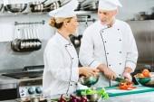 Fotografie ženské a mužské kuchaři v rovnoměrné řezání ingredience při vaření v kuchyni restaurace