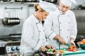 Fotografie usmíval se ženské a mužské kuchaři v rovnoměrné řezání ingredience při vaření v kuchyni restaurace