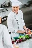 smiling male chef in uniform cutting vegetables in restaurant kitchen