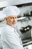 gut aussehend lächelnd männlichen Chef in Uniform und GAP Blick in die Kamera in der Restaurantküche