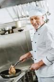 usmívající se muž šéfkuchař při pečení maso steak v restauraci kuchyni při pohledu na fotoaparát