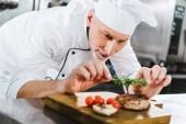Fotografia fuoco selettivo del cuoco unico maschio in uniforme decorazione bistecca di carne al rosmarino nella cucina del ristorante