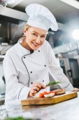 krásná žena kuchař v uniformě zdobí maso steak s rozmarýnem v kuchyni restaurace