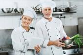 ženské a mužské kuchaři v iniforms při pohledu na fotoaparát a pomocí digitálních tabletu při vaření v kuchyni restaurace