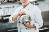 verkürzten Blick auf männlichen Chef in Uniform mit Serviertablett mit Kuppel in Restaurantküche
