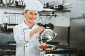 krásná usměvavá žena kuchař v uniformě drží dome od servírovací podnos s masité jídlo v kuchyni restaurace