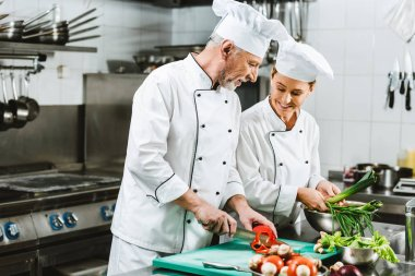 smiling female and male chefs in uniform and hats cooking in restaurant kitchen