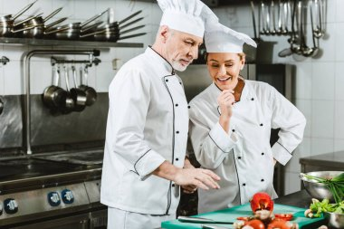 female and male chefs in uniform having conversation while cooking in restaurant kitchen