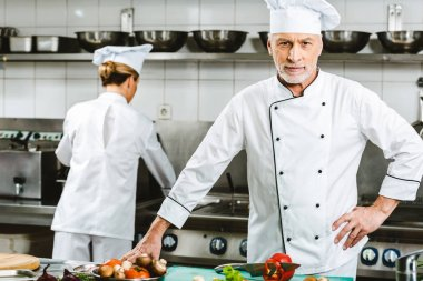 pensive male chef in uniform looking at camera during cooking in restaurant kitchen with female colleague on background