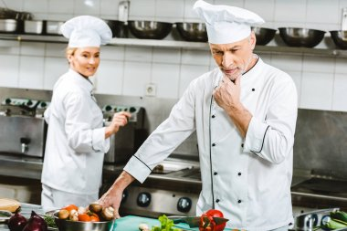 selective focus of pensive male chef in double-breasted jacket during cooking in restaurant kitchen with female colleague on background