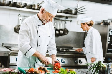 selective focus of male and female chefs in uniform preparing food in restaurant kitchen
