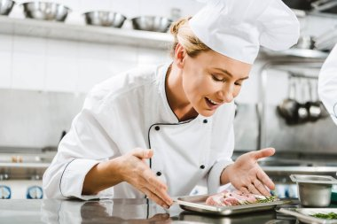 beautiful female smiling chef in uniform holding plate with meat dish in restaurant kitchen